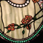 Drapery glass for the dress, opalescent glass for the blossoms, streaky glass in the border, confetti glass in the background and what may be iridescent glass in the beads.
